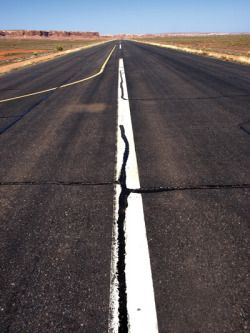A long road with a lot of cracks and potholes in it