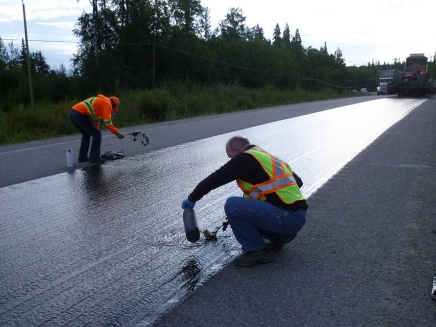 Workers sealcoating the highway